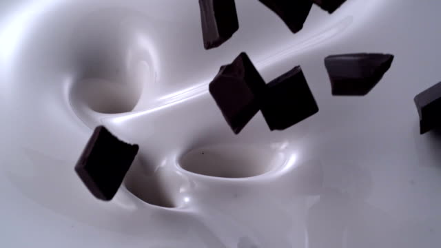 chocolate pieces falling into a creamy milk swirl - milk stock videos & royalty-free footage