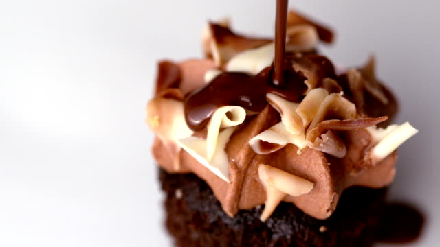 chocolate sauce pouring over muffin - indulgence stock videos & royalty-free footage
