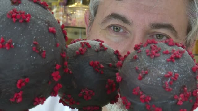chocolate shell sprinkled with red almonds an edible representation of the new coronavirus made by french chocolatier jean francois pre who took his... - sprinkling stock videos & royalty-free footage