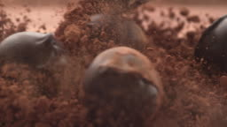Chocolate truffles falling into chocolate powder in super slow motion.