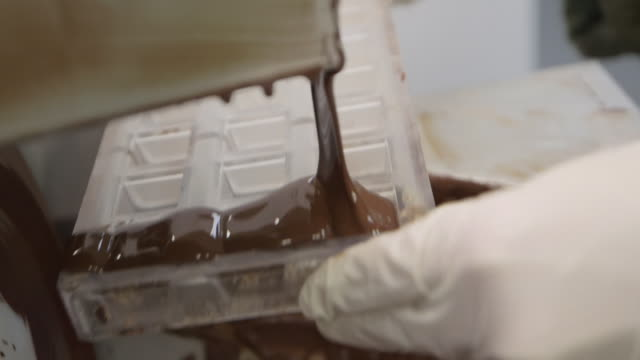 chocolatier's kitchen - tempered chocolate being poured into a mold - pour spout stock videos & royalty-free footage