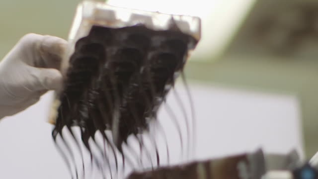 chocolatier's kitchen - tempered chocolate being poured into a mold - moulding a shape stock videos & royalty-free footage