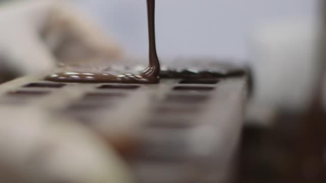 stockvideo's en b-roll-footage met chocolatier's kitchen - tempered chocolate wordt gegoten in een mal - ingrediënt