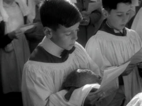 choir boy holds a tortosie as he sings at an open air church service in honour of st francis. 1952. - singing stock videos & royalty-free footage