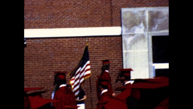 choir dressed in white singing on stage at graduation ceremony graduates in red cap and gown sitting in the audience graduates walking on stage... - red cap stock videos & royalty-free footage