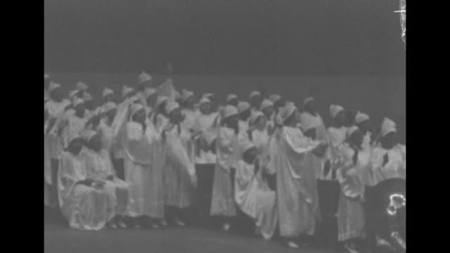 Choir singing and clapping hands in unison pan across choir to Elder Lightfoot Solomon Michaux leading it / closer view of Michaux leading choir /...