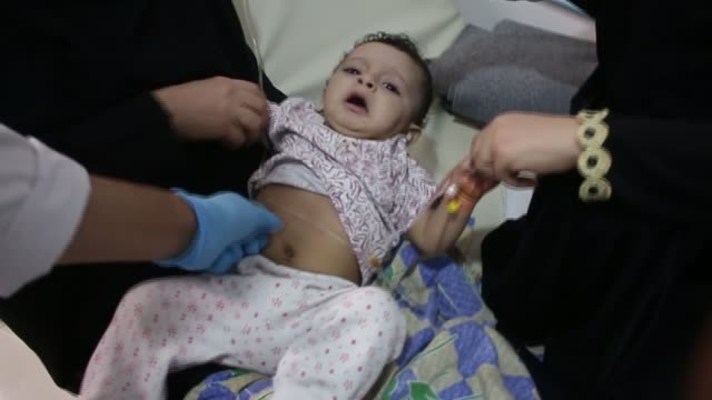 vídeos de stock, filmes e b-roll de sana'a al sabeen hospital int doctor treating sick child suffering from cholera in hospital ward sick child crying as examined by doctor sick child... - tossindo