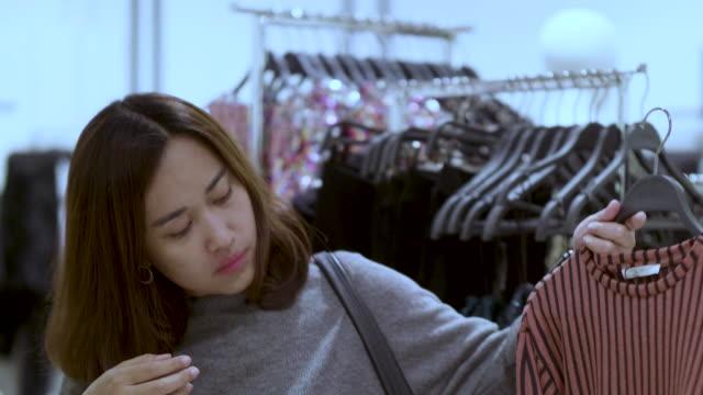 Choosing dress in a boutique