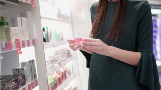 choosing facial creme in pharmacy - make up stock videos & royalty-free footage
