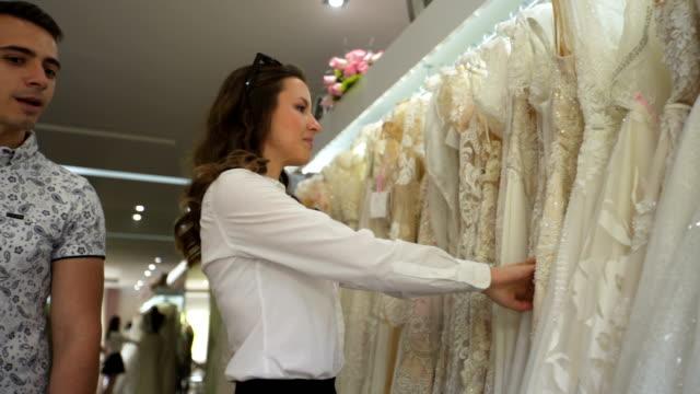 vídeos de stock, filmes e b-roll de escolhendo vestido de casamento em loja de noivas - conveniência