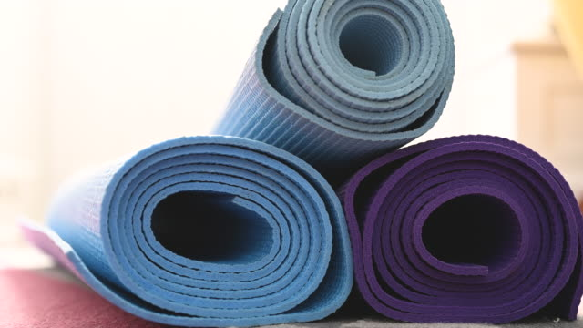 choosing yoga mat from pile - one mid adult woman only stock videos & royalty-free footage