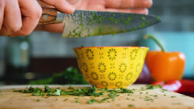 chopped coriander is placed in a yellow bowl - kräuter stock-videos und b-roll-filmmaterial