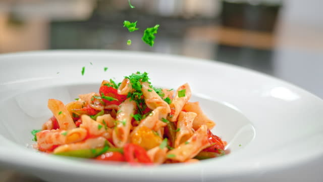 slo mo td chopped fresh parsley falling onto pasta - food stock videos & royalty-free footage