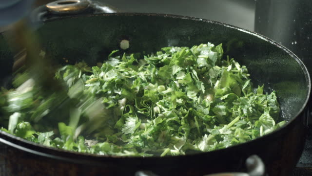 vídeos de stock, filmes e b-roll de ecu chopped garlic tossed into frying pan and stirred with chopped parsley mixed in - skillet cooking pan