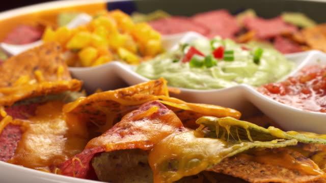 vídeos y material grabado en eventos de stock de cu chopped olives and chopped scallions being sprinkled over nachos on appetizer plate / los angeles, california, united states - aperitivo plato de comida
