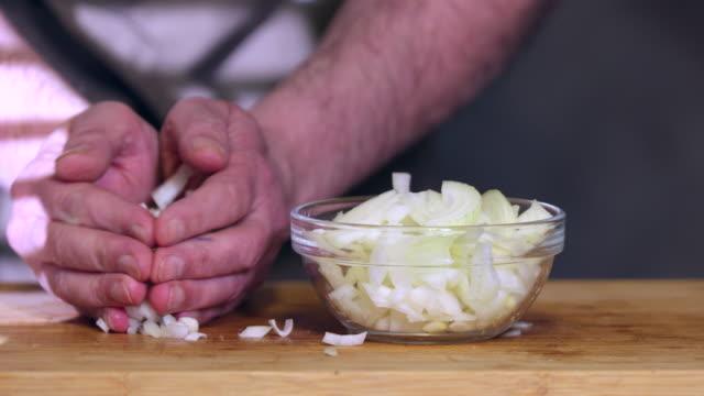 vídeos de stock e filmes b-roll de chopped onion in bowl. - só homens maduros
