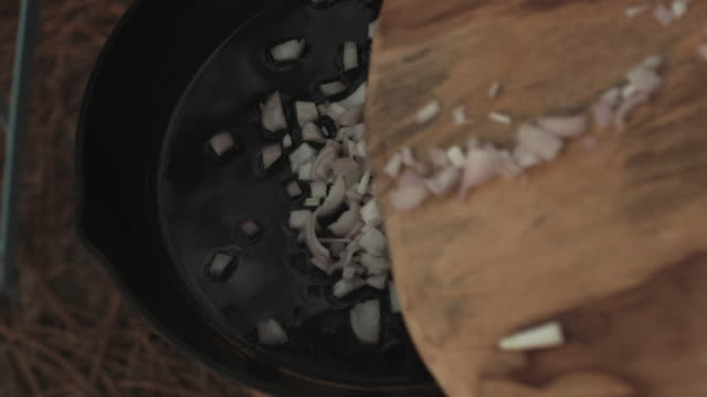 chopped onions and olive oil in cast iron skillet. - saute stock videos and b-roll footage