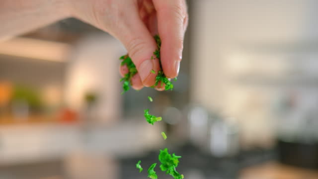 slo mo td chopped parsley falling onto a plate of pasta - 30 seconds or greater stock videos & royalty-free footage