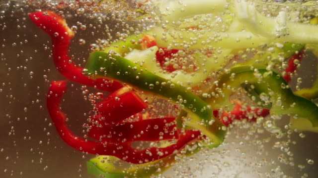 Chopped red, green and yellow bell pepper falling down into boiling water