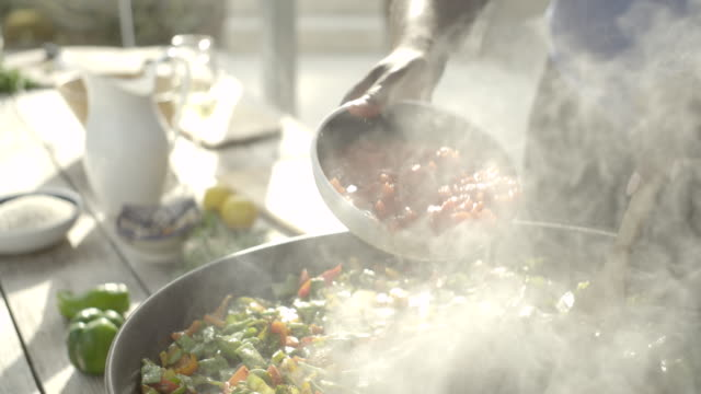 chopped tomatoes are poured into a paella pan - garkochen stock-videos und b-roll-filmmaterial