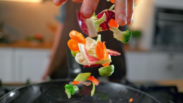 vidéos et rushes de slo mo td légumes hachés jetés dans une casserole - lancer