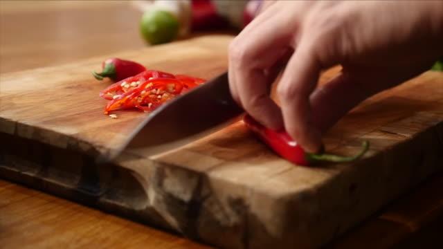chopping a chilli pepper - 赤唐辛子点の映像素材/bロール