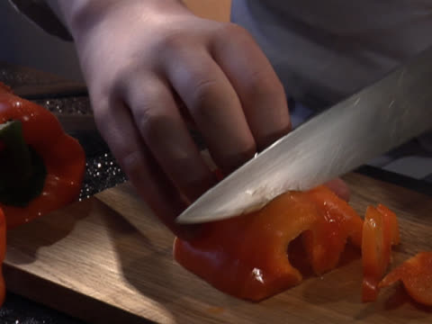 chopping a red bell pepper on a wooden board - unknown gender stock videos & royalty-free footage