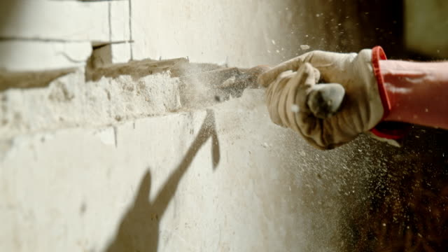 SLO MO Chopping away the concrete with a bricklayer's hammer