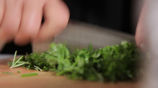 chopping cilantro in small pieces - cilantro stock videos and b-roll footage