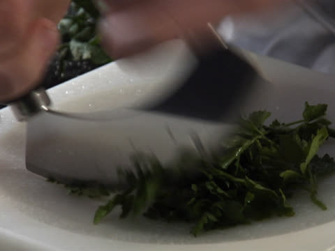 chopping fresh parsley with a mezzaluna - parsley stock videos and b-roll footage