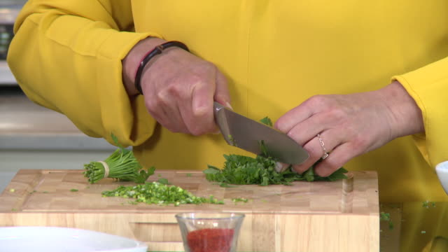 chopping parsley. view of a woman's hands chopping parsley. - kitchen worktop stock videos & royalty-free footage