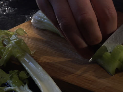 chopping two celery stalks on a wooden board - unknown gender stock videos & royalty-free footage
