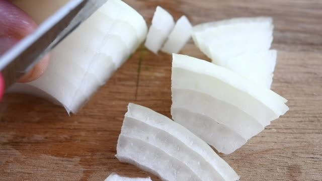 Chopping white onion in a wooden cutting board, slow motion