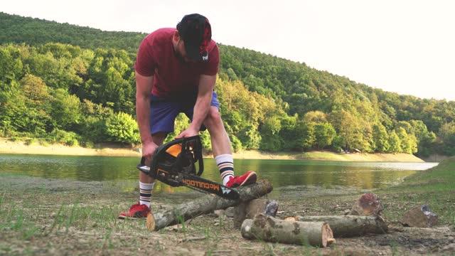 vídeos de stock, filmes e b-roll de cortando madeira com motosserra na floresta - forester