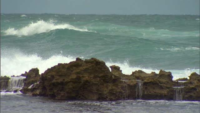 choppy ocean/sea waves rising, rolling, white caps breaking behind line of exposed boulder rocks fg. no land, no people, caribbean region. - boulder rock video stock e b–roll