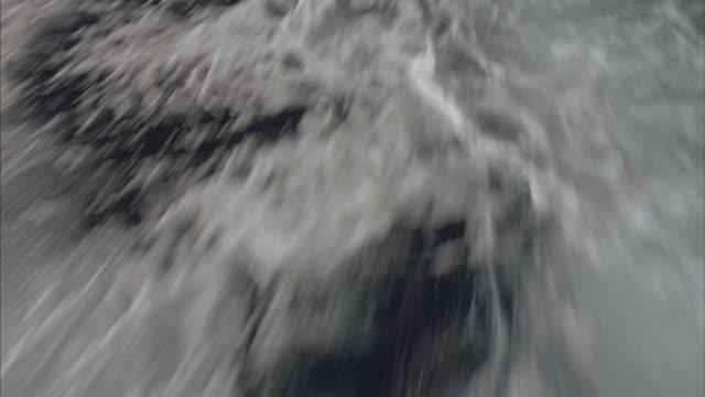 POV of choppy water as sailboat moves through the ocean.