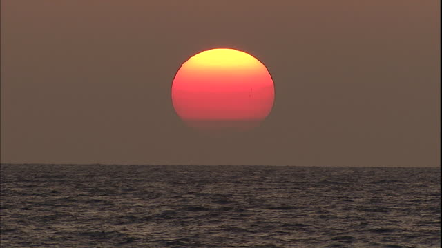 Choppy waves move under a vibrant orange sun.