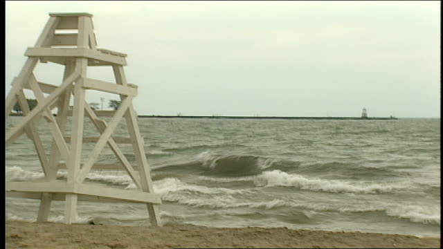 choppy waves on beach and empty lifeguard chair in chicago, illinois - lifeguard chair stock videos & royalty-free footage