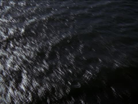 choppy waves roll across the surface of an ocean. - b roll stock-videos und b-roll-filmmaterial