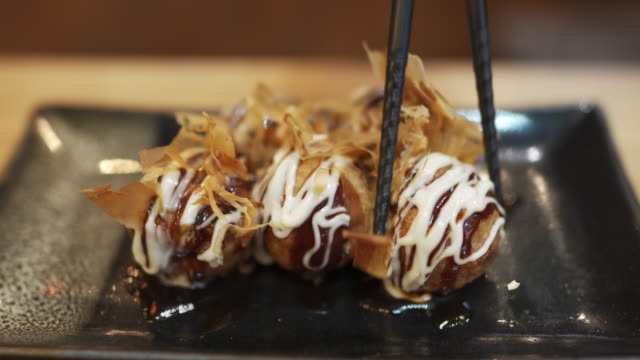stockvideo's en b-roll-footage met eetstokje dat takoyaki plukt, balvormige japanse snack - voorgerecht