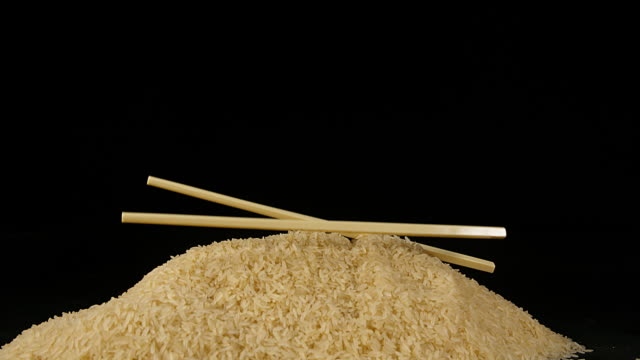chopsticks falling on rice against black background, slow motion 4k - bacchette cinesi video stock e b–roll