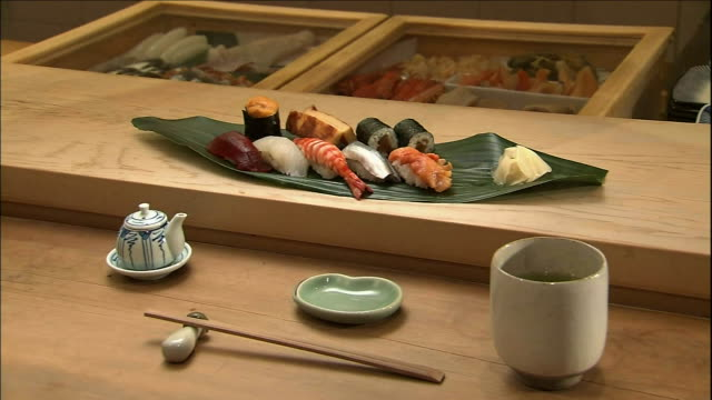 chopsticks, green tea and a platter filled with sushi sits on the counter of a sushi shop. - nigiri stock videos and b-roll footage