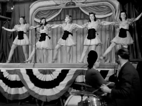 Chorus girls in short dresses aprons on stage dancing WS Women watching dancing WWII