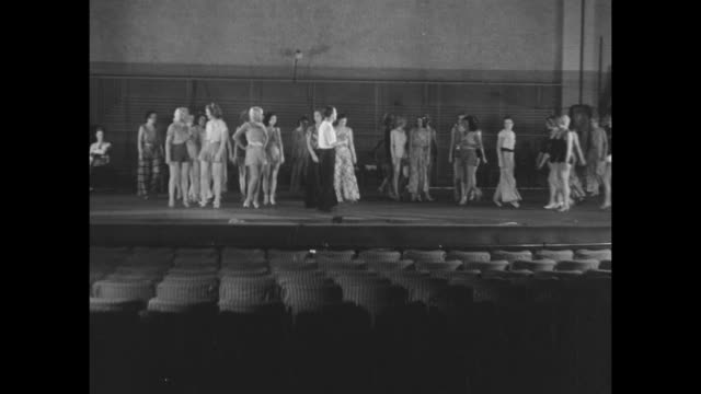 WS chorus girls sitting on chairs on stage waiting producer/director George White walks onto stage girls stand and walk to positions in chorus line...