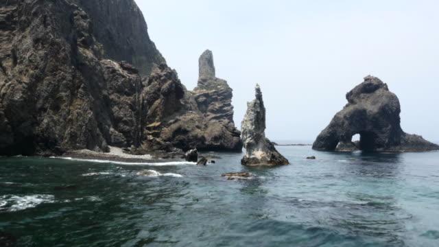 vidéos et rushes de chotdaebawi rock and samhyeongjegulbawi boulder (three brothers cave rock) and tanggeonbong peak in seodo (western island) of dokdo island / ulleung-gun, gyeongsangbuk-do, south korea - boulder rock