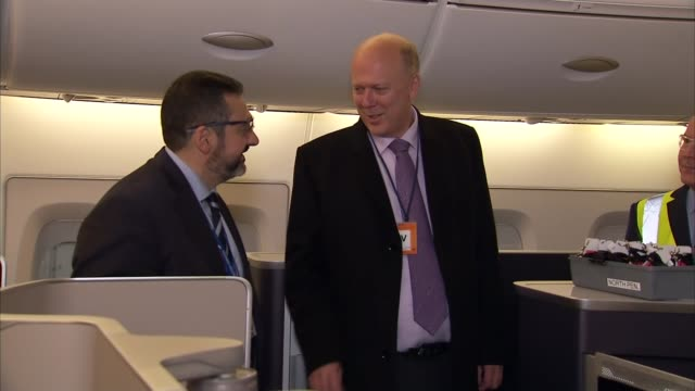 London Heathrow Airport INT Chris Grayling MP along through hangar chatting with staff / Planes in hangar / Chris Grayling and others along inside...