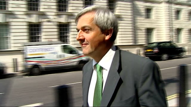 chris huhne denies he dodged penalty points for speeding; t04051124 ext huhne along and crossing road - クリス ヒューン点の映像素材/bロール