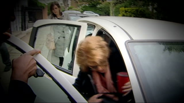 chris huhne resigns from cabinet to face charges of perverting the course of justice lib vicky pryce getting in car as surrounded by press - ビッキー・プライス点の映像素材/bロール