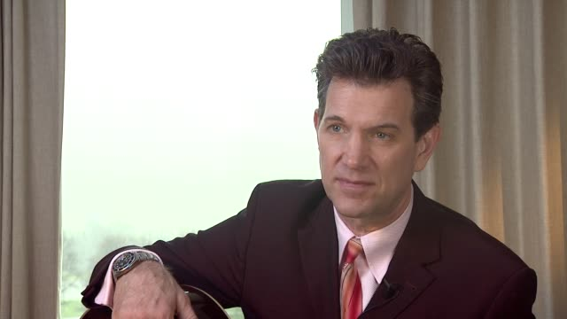 vídeos de stock, filmes e b-roll de chris isaak on the different approaches of music artists and how he prefers rock n' roll at chris isaak interview the royal garden hotel on 24th... - chris isaak