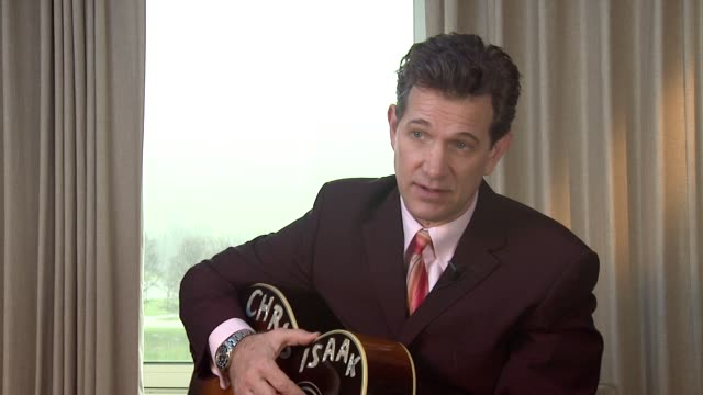 vídeos de stock, filmes e b-roll de chris isaak on the music and style he had when he was young that was different to the rest to at chris isaak interview the royal garden hotel on 24th... - chris isaak